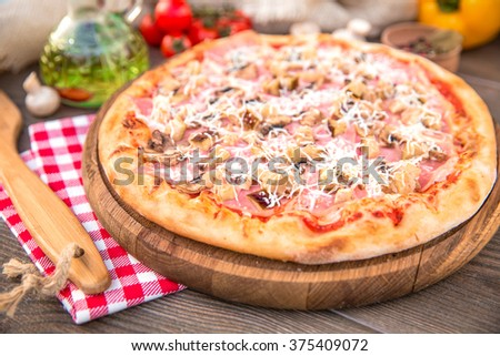 Italian Pizza with ham, mushrooms and different spices - stock photo