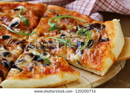 Italian pizza with mushrooms and olives on a wooden board - stock photo