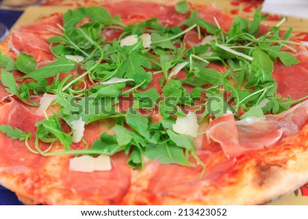 Italian pizza with parmesan, rucola and prosciutto closeup view  - stock photo