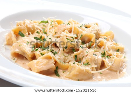 Italian ravioli tortellini with cream sauce and basil and parmesan cheese on a white plate isolated - stock photo
