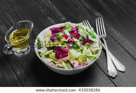 Italian salad with freshly harvested organic vegetables including varieties of lettuce Iceberg, Radic, Frisse with Italian dressing for salad of lettuce, silver forks on a dark black wooden background - stock photo