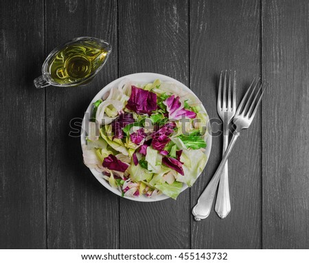 Italian salad with freshly harvested organic vegetables including varieties of lettuce Iceberg, Radic, Frisse with Italian dressing for salad of lettuce, dark black wooden background, top view - stock photo
