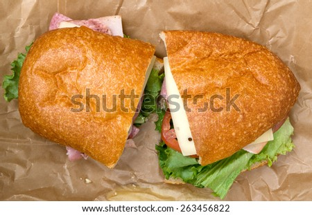 Italian sandwich with ham, salami, turkey, swiss cheese, lettuce, tomato and mayonnaise on ciabatta bread, sitting on butcher paper.  - stock photo