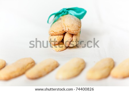 Italian savoiardi cookies tied with a blue ribbon and a line of cookies in the foreground. - stock photo