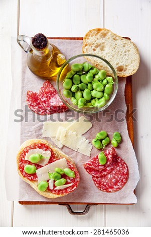 Italian snacks. salami sandwich with parmesan cheese & broad beans. white dry wine. Traditional Roman appetizer - stock photo