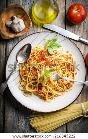 Italian spaghetti on rustic wooden table - stock photo