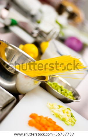 italian spaghetti pasta on a typical full equipped restaurant kitchen - stock photo