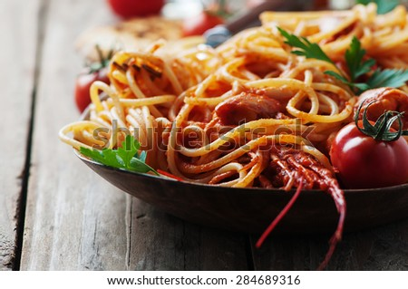 Italian spaghetti with shrimps and tomato, selective focus - stock photo