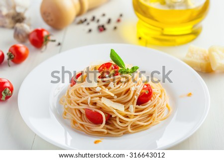 Italian spaghetti with tomato sauce, parmsesan cheese and basil on table