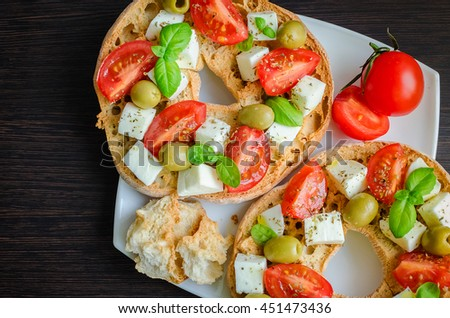 Italian starter friselle. Classical frisella tomato, cheese mozzarella, olives and basil with oregano and olive oil. Dried bread called freselle on white plate. Italian food. Healthy vegetarian food. - stock photo