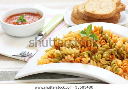 italian style fresh pasta with tomato and basil leaf decoration - stock photo