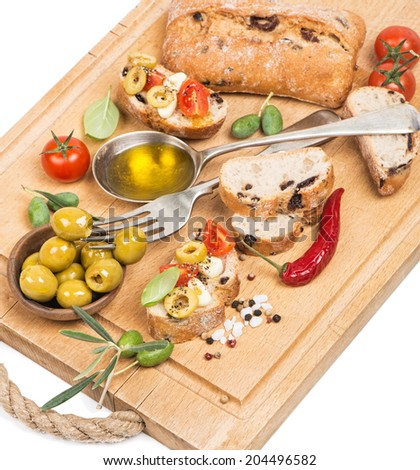 Italian tomato bruschetta with chopped olives, garlic, herbs and olive oil  on a wooden kitchen board - stock photo