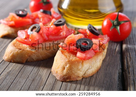 Italian tomato bruschetta with chopped vegetables, herbs and oil on grilled baguette - stock photo