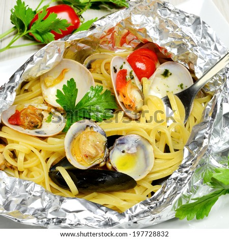 italian traditional food composed by spaghetti pasta and seafood fasolari,clams and mussels, cooked in oven in aluminium - stock photo