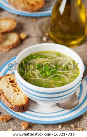 Italian traditional green pea soup with pasta and mint, selective ficus - stock photo