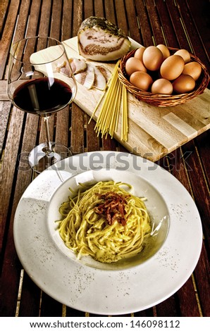 Italian traditional recipe, spaghetti alla carbonara with ingredients on background and a glass of red wine - stock photo