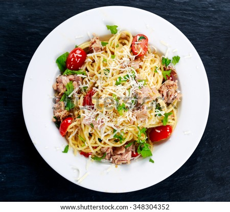 Italian Tuna Pasta spaghetti with tomato, chili, Parmesan cheese and wild rocket lives. on old blue stone background. - stock photo