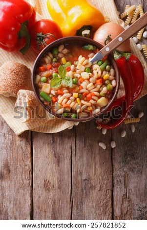 Italian vegetable minestrone soup in a bowl and ingredients on the table. vertical top view