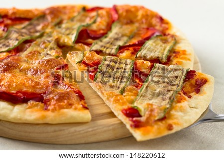 Italian vegetarian pizza lifted slice with pepper and zucchini - stock photo
