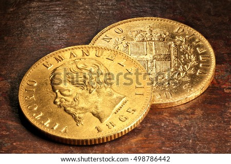 Italian Victor Emmanuel II gold coins on rustic wooden background