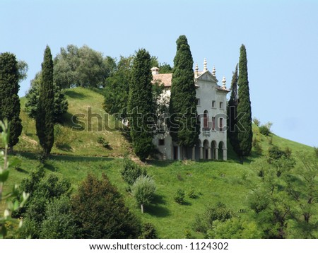 Italian Villa and Cypress trees on hill in Italy