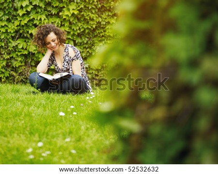 italian woman reading book on grass and smiling. Horizontal shape, copy space - stock photo