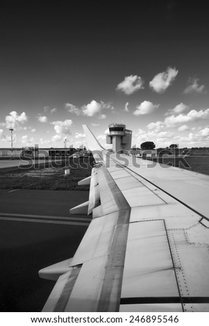 Italy, airplane wing and flight control tower in an airport - stock photo