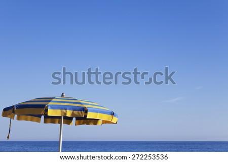Italy, Liguria, sunshade at beach, blue sky - stock photo