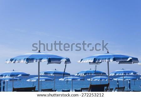 Italy, Liguria, sunshades at beach, blue sky - stock photo