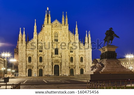 Italy Milan central city cathedral square at sunrise view on Milan duomo facade illuminated by street lamps with horse statue on the right - stock photo
