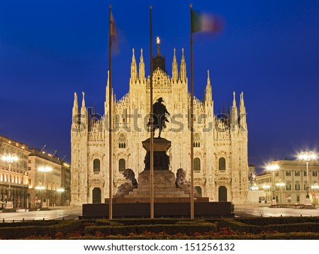 Italy Milan Lombardi duomo cathedral landmark illuminated facade at sunrise with 3 frags and horse statue monument  - stock photo