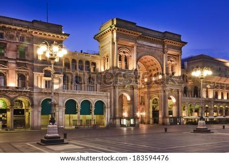 Italy Milan Vittorio Emmanuel Passage luxury shopping mall main gate entrance at sunrise fully illuminated - stock photo