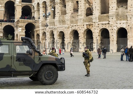 ITALY, ROME - JANUARY 22, 2017: Armed Italian anti terrorist soldiers patrol near the Colosseum. Colosseum  is the largest amphitheater ever built, made of concrete and sand.