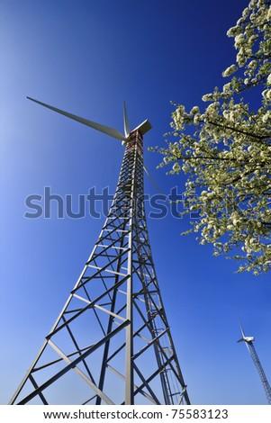 ITALY, Sicily, Catania province, countryside, Eolic energy turbines and almond tree - stock photo