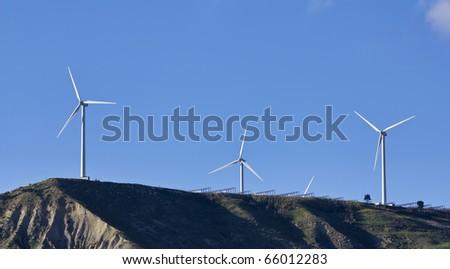 ITALY, Sicily, countryside near Agrigento, Eolic energy turbines and solar mirrors - stock photo