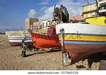 Italy, Sicily, Mediterranean sea, Punta Secca (Ragusa Province), wooden fishing boats ashore - stock photo