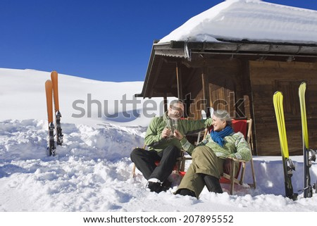 Italy, South Tyrol, Seiseralm, Senior couple sitting in front of log cabin, holding champagne glasses - stock photo