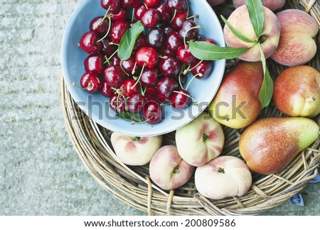 Italy, Tuscany, Magliano, Close up of peach pears and cherries in basket, elevated view