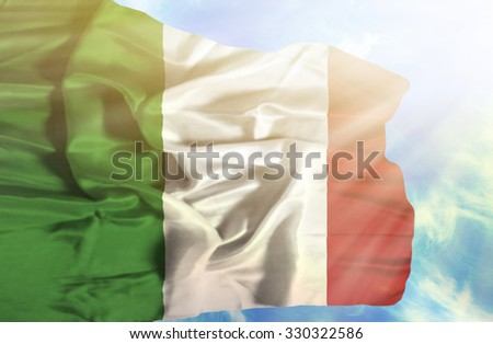 Italy waving flag against blue sky with sunrays - stock photo