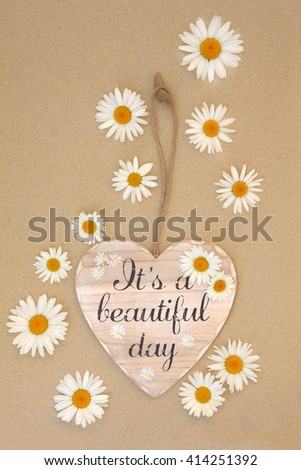 Its a beautiful day sign with daisy flowers on beach sand background. - stock photo