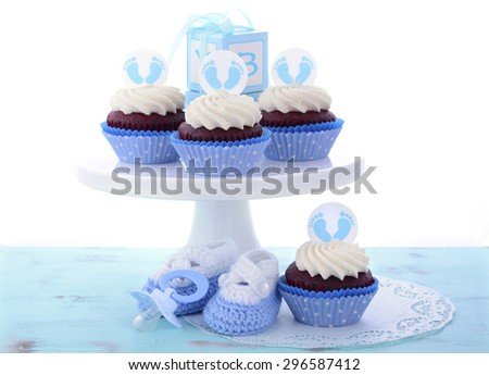 Its a Boy Blue Baby Shower Cupcakes with baby feet toppers and decorations on shabby chic blue wood table.  - stock photo