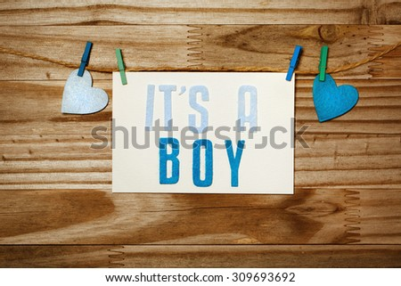 ITS A BOY card and felt hearts hanging with clothespins - stock photo