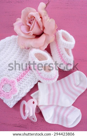 Its a Girl Baby Shower or Nursery layout with bonnet, booties, socks and silk rose on pink shabby chic table.  - stock photo