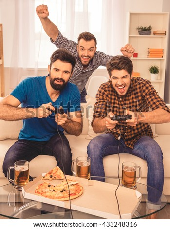 Its a win! excited happy cheerful men play video game with beer and pizza - stock photo