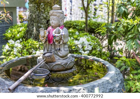 Itsukushima, Japan - April 27, 2014: A purification fountain in Daisho-in temple. At the entrance of Buddhist and Shinto temples in Japan, there is a fountain that people can use for purification. - stock photo