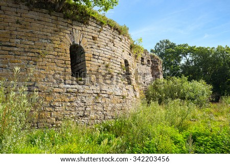 Ivangorod Fortress Ruins. The round corner tower with loopholes. - stock photo