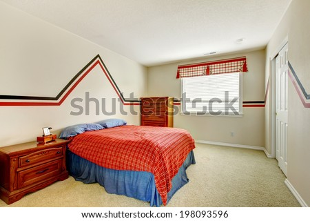 Ivory bedroom with painted walls, wooden nightstand and dresser. VIew of bed in bright blue and right colors