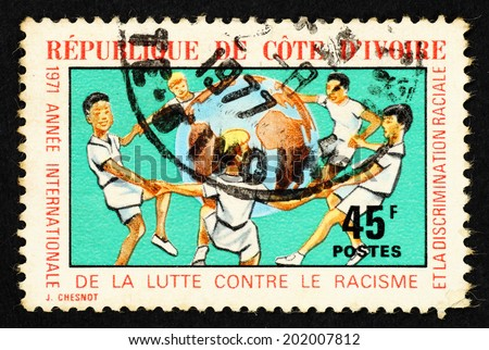 IVORY COAST - CIRCA 1971: Stamp printed in Ivory Coast with image of children circle over a globe to commemorate the International Year of the fight against racism and racial discrimination. - stock photo