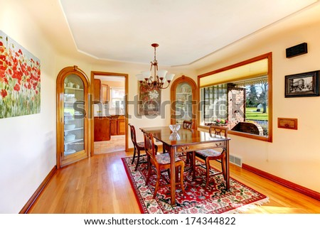 Ivory dining room with big window overlooking front porch. Furnished with rustic wood table set, decorated with old style pictures