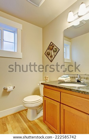 Ivory restroom with hardwood floor and maple vanity cabinet with granite top and mirror